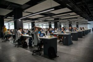 open concept office with dozens of workers on laptops