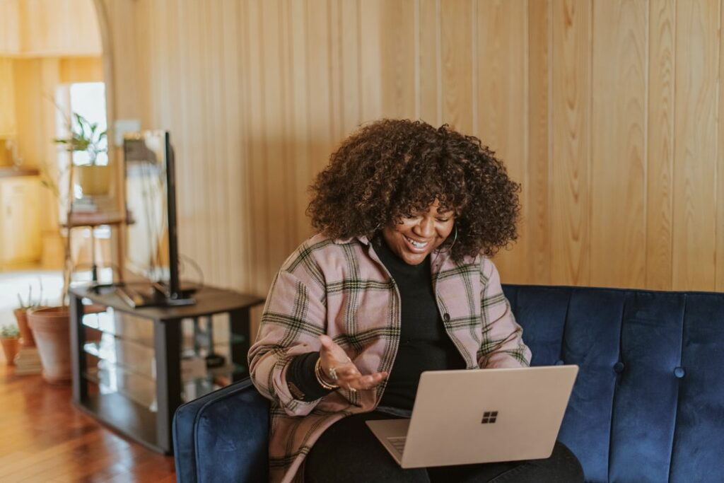 woman smiling and gesturing while looking at laptop